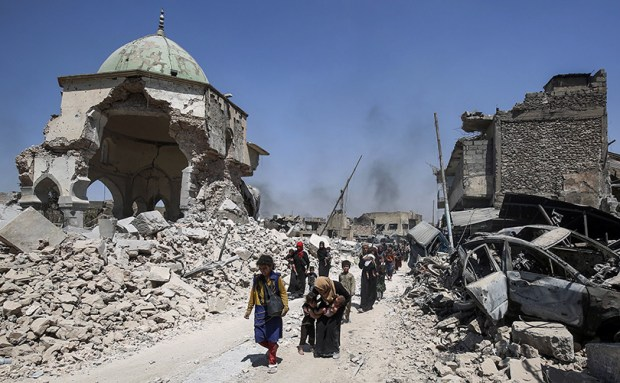 Iraqis walk by the destroyed Al-Nuri Mosque as they flee from the Old City of Mosul on Wednesday during the Iraqi government forces' offensive to retake the city from Islamic State fighters.
