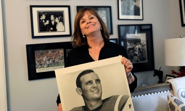 In this Wednesday, July 26, 2017 photo, Lise Hudson poses with photos of her husband, Jim Hudson, who played football for the University of Texas and the New York Jets in the 1960's, at her home in Austin, Texas. After his death, researchers found that Hudson suffered from stage IV chronic traumatic encephalopathy, the highest level of the brain disease.