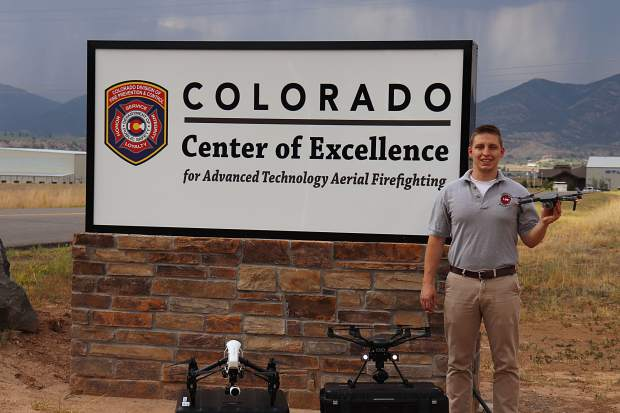 Military and UAS Integration Specialist for the Center of Excellence Garrett Seddon stands with drone that he hopes one day may be used in wildfires.