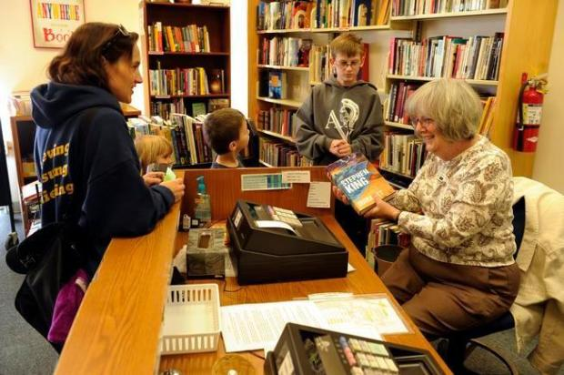 Martha Rodgers, right, checks out Anna Garchow, left, with her family at the Friends of the Aurora Public Library book store on Oct. 29. Friends of the Aurora Public Library is a foundation that supports the city public libraries through sales at its used book store.