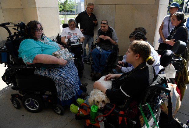 Disabled protesters and supporters gather around ...