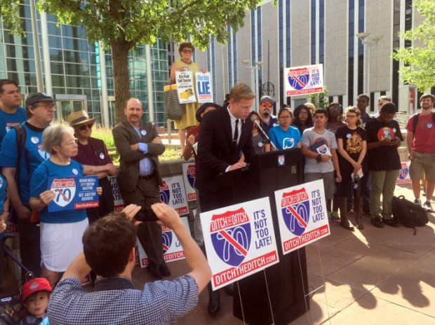 Opponents of the Interstate 70 expansion through northeast Denver flank developer Kyle Zeppelin outside the Alfred A. Arraj United States Courthouse on July 10. Zeppelin spoke during a news conference to announce a lawsuit challenging the project.
