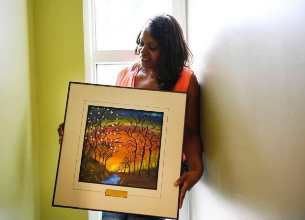 Artist Sevilla Stinnett holds one of ...
