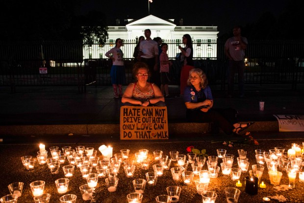 People gather in front of the White House on Sunday for a vigil in response to the events a day earlier in Charlottesville, Va. One woman was killed and 19 injured when a car plowed into a crowd of anti-protesters after a rally by white nationalists.