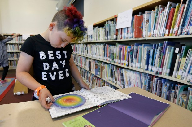 """In this Wednesday, July 12, 2017 photo, Sam, 9, reads a book in the library at Bay Area Rainbow Day Camp in El Cerrito, Calif. The camp caters to transgender and """"gender fluid"""" children, aged 4-12, making it one of the only camps of its kind in the world open to preschoolers, experts say."""