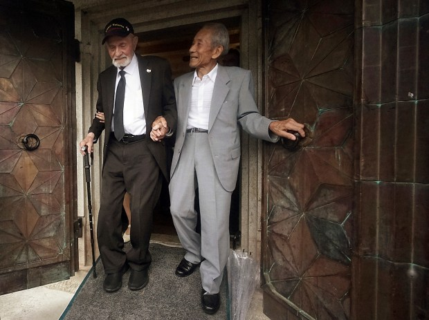 Tatsuya Yasue, right, and WWII veteran Marvin Strombo walk together out from a village's war memorial prior to a ceremony in Higashishirakawa, in central Japan's Gifu prefecture Tuesday, Aug. 15, 2017.