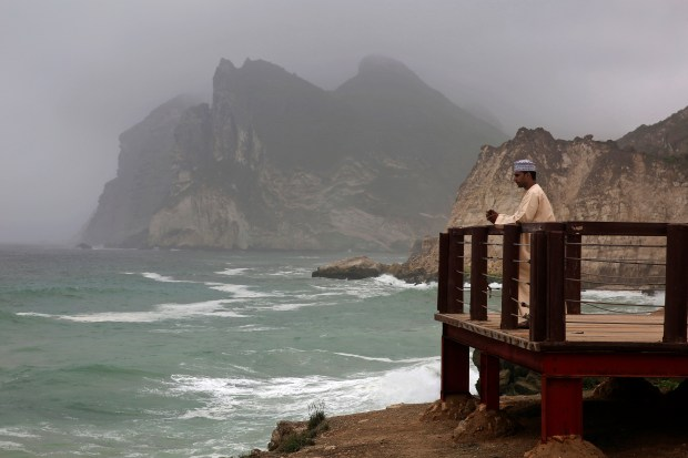 An Omani man films waves crashing onto the rocky shore in al-Maghseel, southern Oman. Oman's foggy monsoon season draws thousands of visitors seeking relief from high temperatures elsewhere in the Arab world.