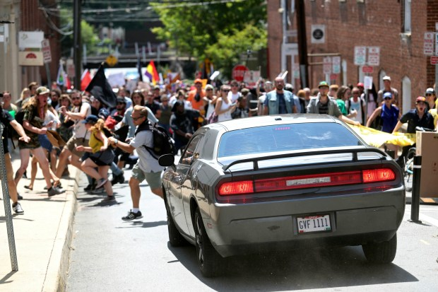 A vehicle drives into a group of protesters demonstrating against a white nationalist rally in Charlottesville, Va., on Aug. 12, killing one and injuring many more. Lawmakers in six states have proposed bills to protect drivers who strike protesters.