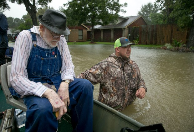 Thomas Luna, right, rescues Bobby Nelson, 78, from his flooded home in the Ravensway neighborhood in northwest Houston on Monday. Luna brought a fishing boat to the neighborhood to assist with the rescue effort.