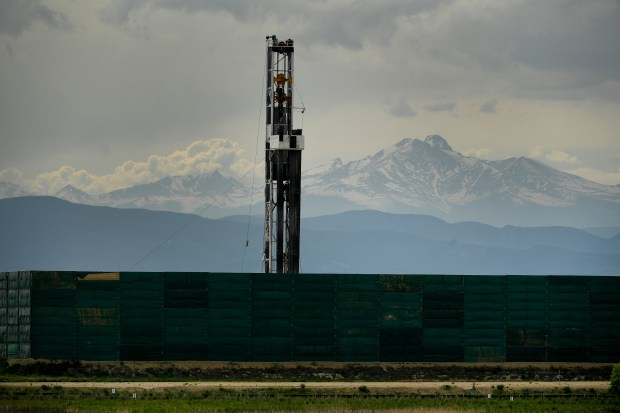 A large Crestone Peak Resources drilling operation, with large noise dampening walls, has Longs Peak in the background near Frederick.