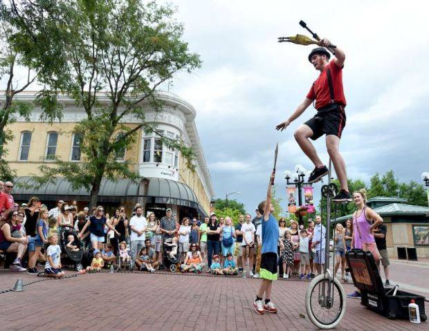 Daredevil Dan Edwards. of Longmont, juggles rides a unicycle at the same time on the Pearl Street Mall. Orson Lee, 8, hands Dan his sword for juggling.