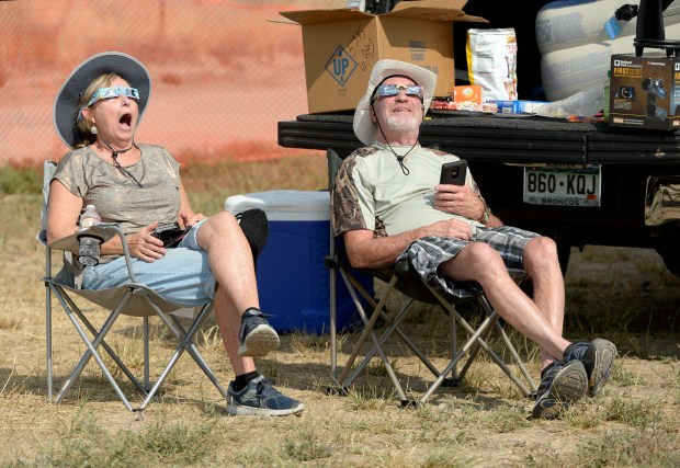 Alice Baer and her brother Bill, from Denver, watch the solar eclipse as it goes into totality on the Wind River Indian Reservation in Wyoming on Monday.
