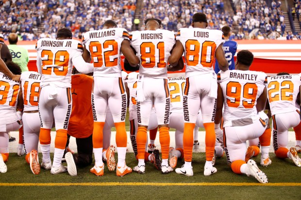 Members of the Cleveland Browns stand and kneel.
