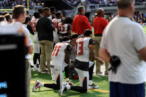 Wide receivers Mike Evans and DeSean Jackson take a knee during the national anthem before the game against the Minnesota Vikings.