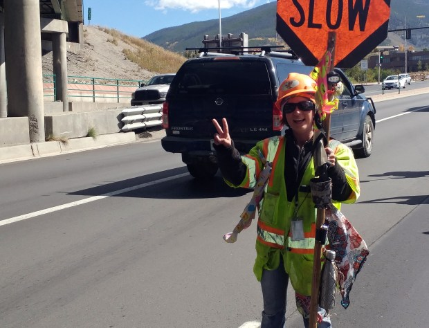 Valerie McCarthy flashes a peace sign at drivers on Colorado 9 in Summit County.