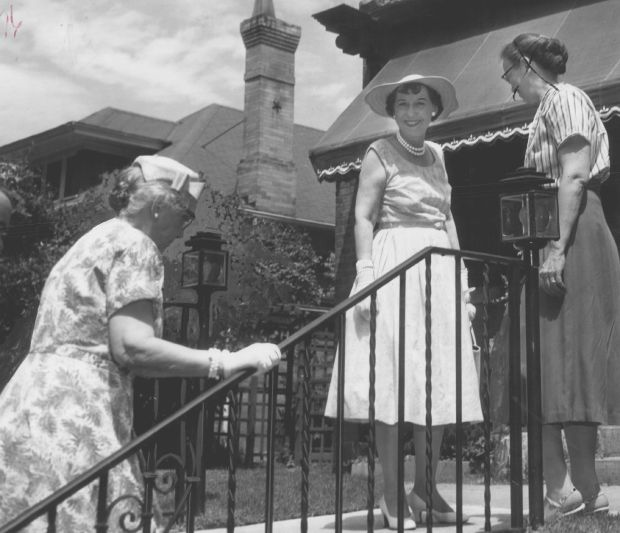 First Lady Mamie Eisenhower poses in front of the Doud family home at 750 Lafayette St. as her mother, Mrs. Elivera Doud climbs the railed steps in August 1957.
