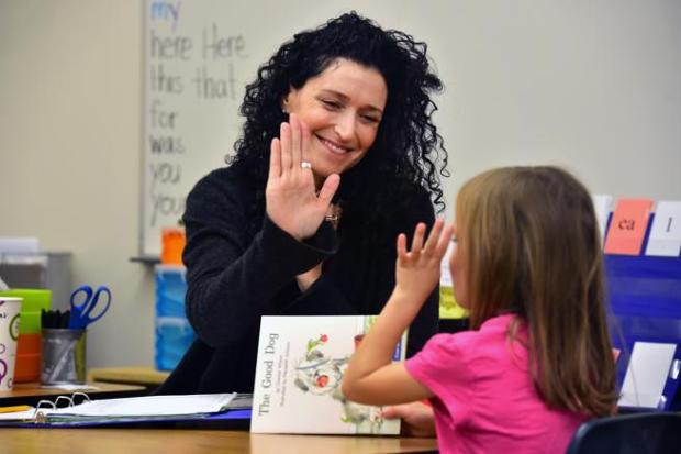 "Boulder teacher Cara Mentzel gives a high-five to her student, Lila Robbie, during class at Foothill Elementary on Oct 6. Mentzel, sister of Broadway star Idina Menzel, penned a memoir, ""Voice Lessons: A Sisters Story."" She'll be at the Boulder Book Store on Tuesday to sign copies."