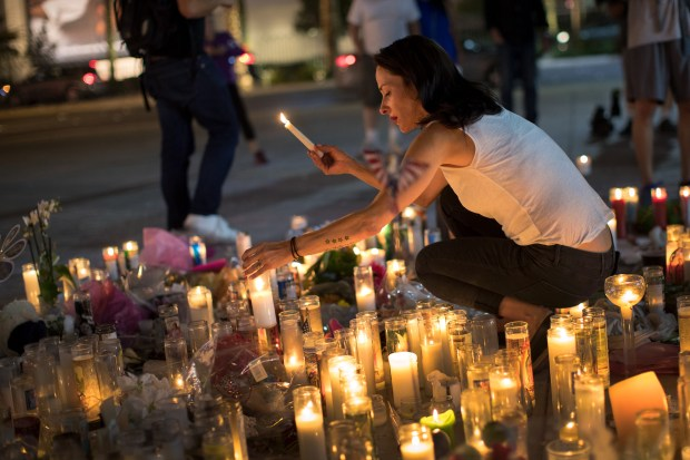 Las Vegas resident Elisabeth Apcar lights candles on Wednesday at a makeshift memorial for the victims of Sunday night's mass shooting.