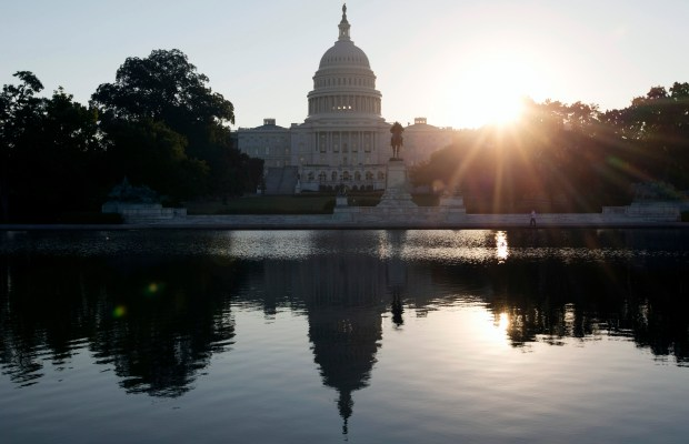 The U.S. Capitol is reflected in the Capitol Reflecting Pool at sunrise in Washington, D.C., on Oct. 2, 2013.