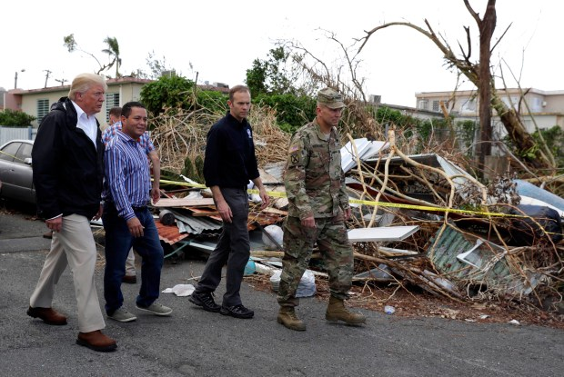President Donald Trump walks with FEMA administrator Brock Long, second from right, and Lt. Gen. Jeff Buchanan, right as he tours an area affected by Hurricane Maria in Guaynabo, Puerto Rico, on Tuesday.