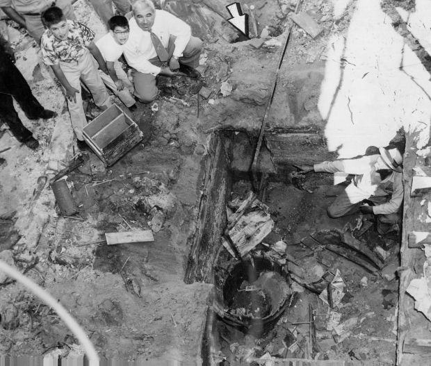 Foreman John Strausheim, right, points to a tunnel leading into a secret basement room fully equipped as a bootleg whiskey plant in June 1954. Broken wooden barrels, layers of debris, water and gas lines, a gas stove and The Denver Post for Aug. 27, 1933, were found in the room, which was uncovered by workmen razing a building at 2033 Champa St.