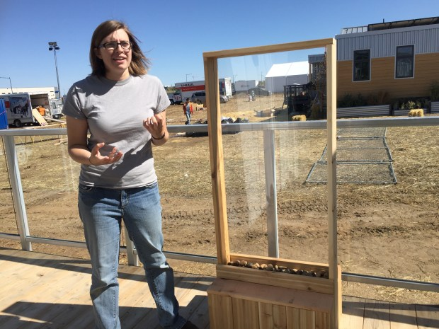 Missouri University of Science and Technology engineering student Jenny Nickel explains a water feature on the deck of her team's solar house, a finalist in this year's Department of Energy Solar Decathlon competition. Gray water recycled from showers is circulated under the deck and through filters to keep it from getting contaminated before it's used to water plants.