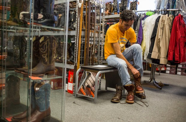 Yair Recéndez Solís, a temporary migrant worker from Mexico, shops for a new pair of boots.