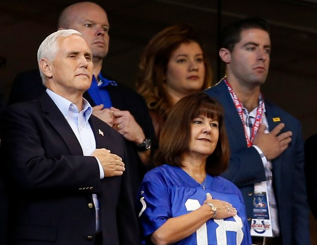 Vice President Mike Pence covers his heart along with his wife, Karen, right, during the national anthem as the Indianapolis Colts host the San Francisco 49ers at Lucas Oil Stadium on Sunday. Pence left after about a dozen San Francisco players took a knee during the national anthem.