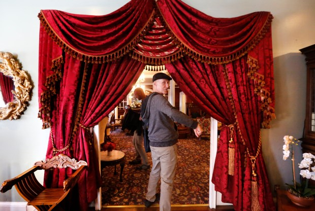 """Host Jay Gifford leads participants into the main lobby of the Queen Anne Hotel in San Francisco, Calif., during the Victorian Home Walk tour on Friday, Sept. 15, 2017. Airbnb's new """"experiences"""" feature allows people to use the platform to plan experiences as well as places to stay."""