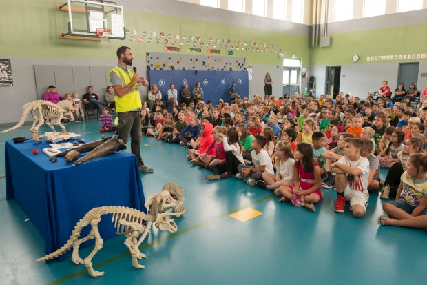 A photo of Joe Sertich talking to elementary school kids with dinosaur models in the background