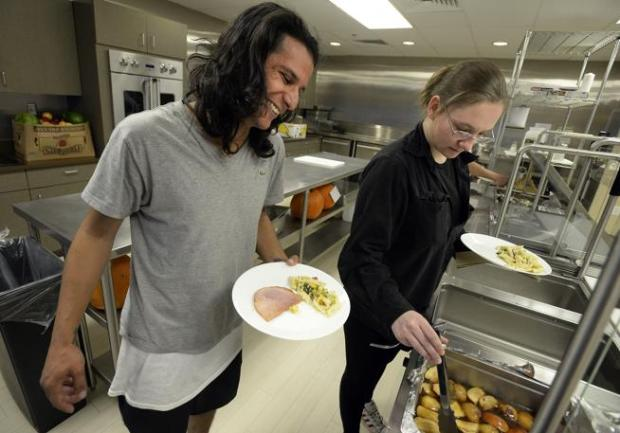 Mat Morrell, left, and Eden Scheppman get lunch on Friday at the Ready to Work House in Boulder. Isabel McDevitt, the executive director of Bridge House, is hoping to expand the program to Aurora.
