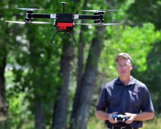 Tim Haynie, owner of Spectrabotics, launches a drone to fly over and photograph ash trees damaged by the emerald ash borer in Boulder in July.