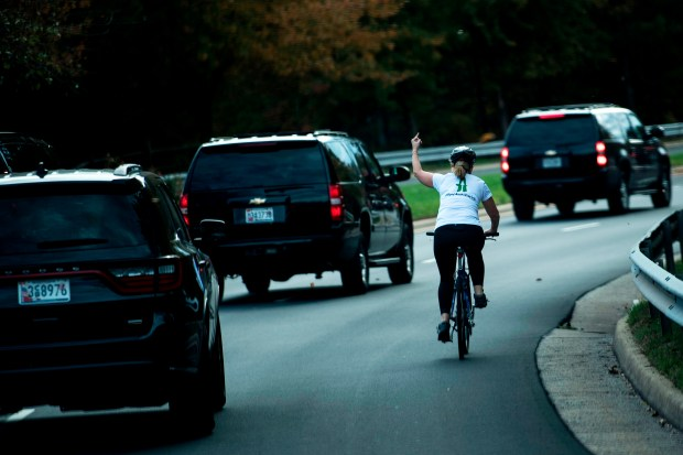 Cylist Juli Briskman gestures with her middle finger as President Donald Trump's motorcade departs Trump National Golf Course in Sterling, Va., on Oct. 28.