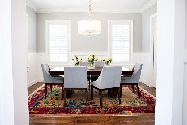 A dining room designed Abbe Fenimore. In dining rooms without drapes, upholstered chairs and a soft rug can bring a sense of warmth that makes holiday entertaining even more appealing, as seen in this dining room designed by Dallas-based interior designer Fenimore.