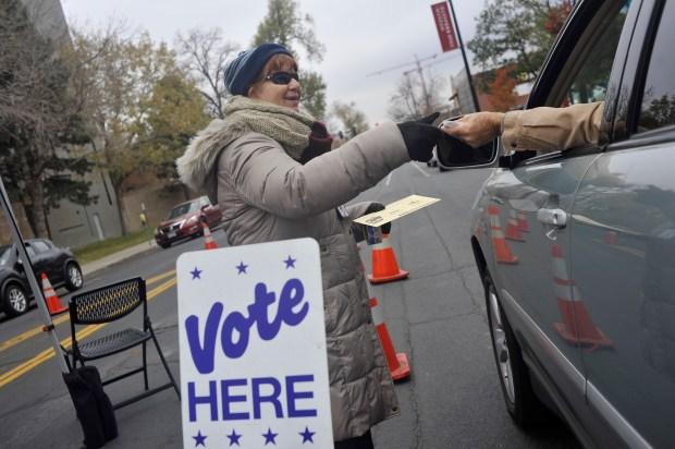 Denver Election Judge Susan Morrison hands ...