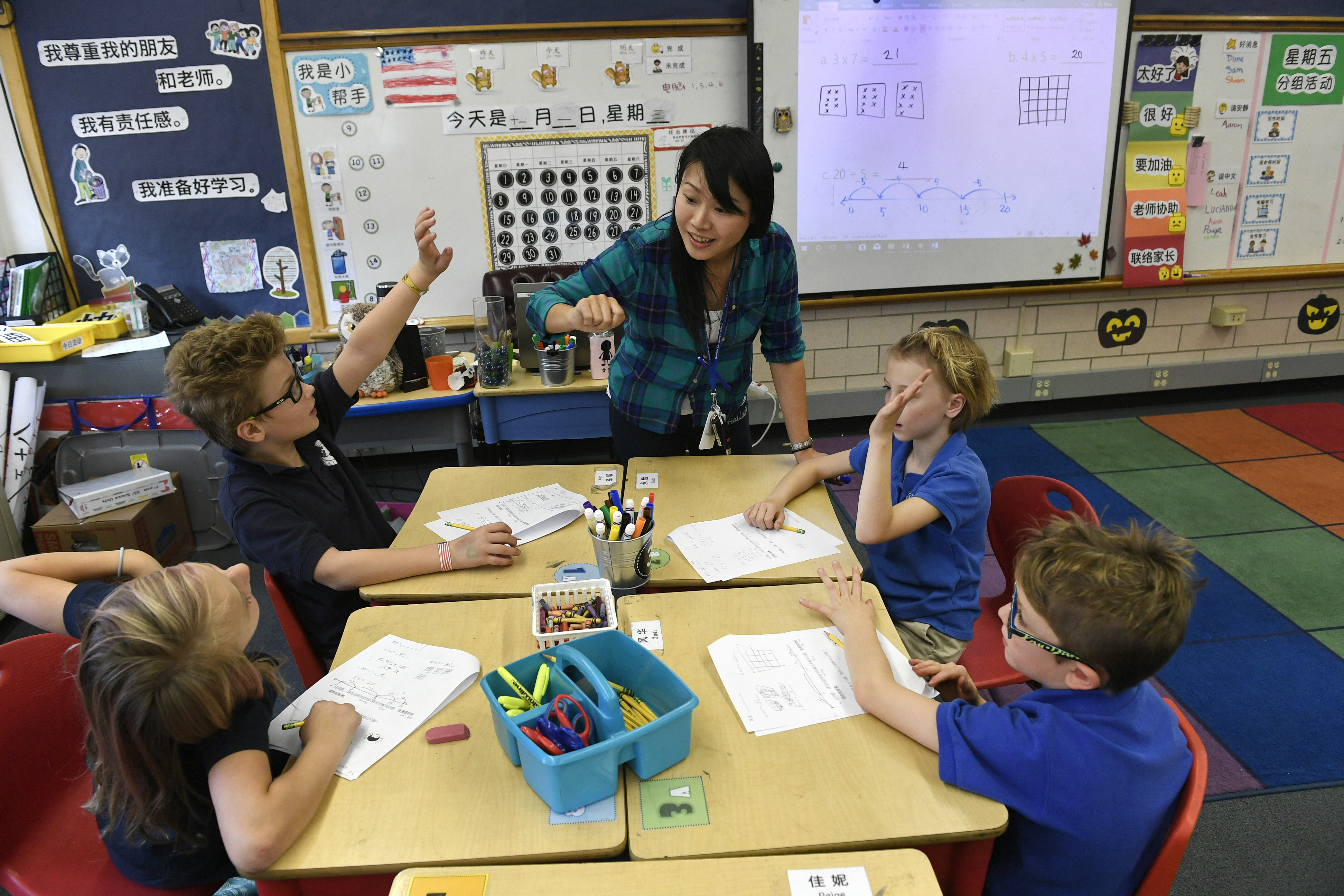 Chinese teacher Yu-Hsin Lien, speaking only in Chinese, helps her 3rd grade students with classwork at the Denver Language School on Nov. 1, 2017 in Denver.