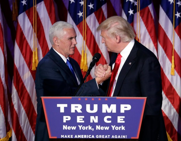 President-elect Donald Trump shakes hands with Vice President-elect Mike Pence as he gives his acceptance speech during the early-morning hours of Nov. 9, 2016, in New York.