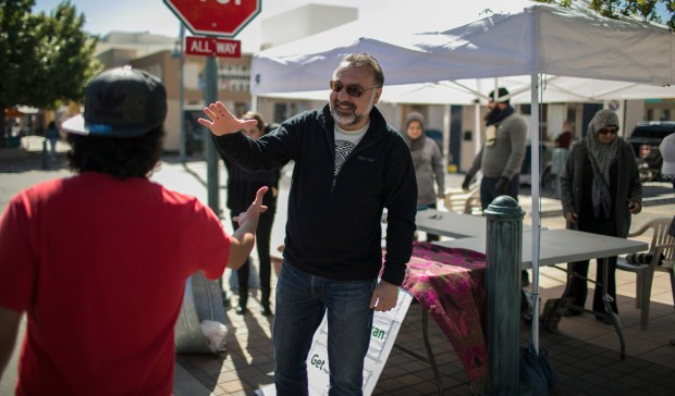 Radwan Jallad, middle, greets a friend during the downtown farmers market in Las Cruces, N.M.