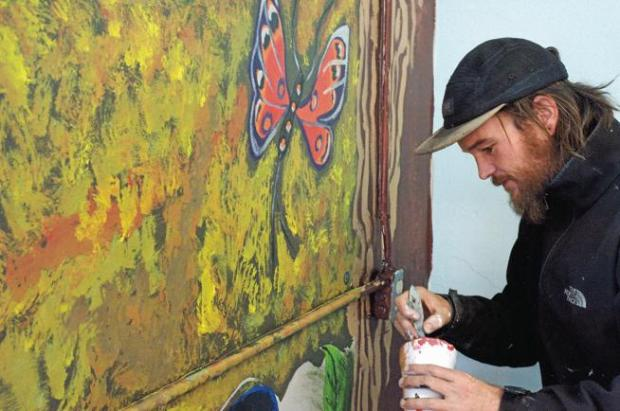 Pueblo artist Mat Taylor, also known as Matte Refic, works on a portion of the mural, 'Dusk to Dawn,' created in conjunction with offenders from the Federal Prison Camp in Florence, at the Museum of Colorado Prisons on Friday, Dec. 15, 2017.