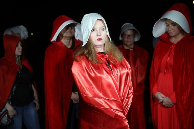 """Ginger Poynter and other women, dressed as characters from the television show """"The Handmaid's Tale,"""" protest Senate candidate Roy Moore on Dec. 5 in Fairhope, Ala. During his campaign, Moore was accused of sexual misconduct by a number of women, including some who had been minors at the time of the alleged misconduct."""