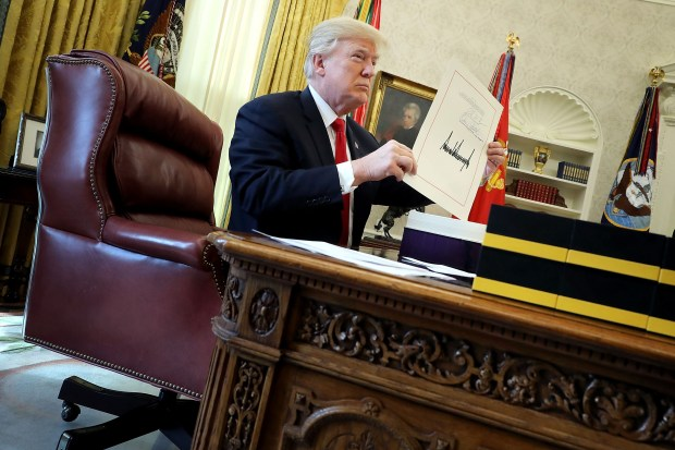President Donald Trump holds up the first page of the Tax Cuts and Jobs Act after signing it into law on Dec. 22 in the Oval Office.