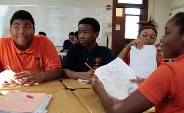 In this Oct. 20, 2017 photo, Jamain Lee, center, looks at classmate Andre'veon Mosby at Milwaukee Math and Science Academy, a charter school in Milwaukee. Next to him is classmate Dreamnoel Haynes, with Brianca Williams facing them. Lee has seen his grades improve since he enrolled two years ago from a school where he was bullied and frequently got into fights.
