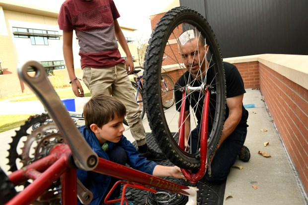 Bike repair teacher Ryan Kelley, right, teaches Max Wood, 10, left, how to fix the brake pads of his bike during a bike workshop that is part of after school activities provided by Impact On Education at Columbine Elementary School on Nov. 1, 2017 in Boulder.