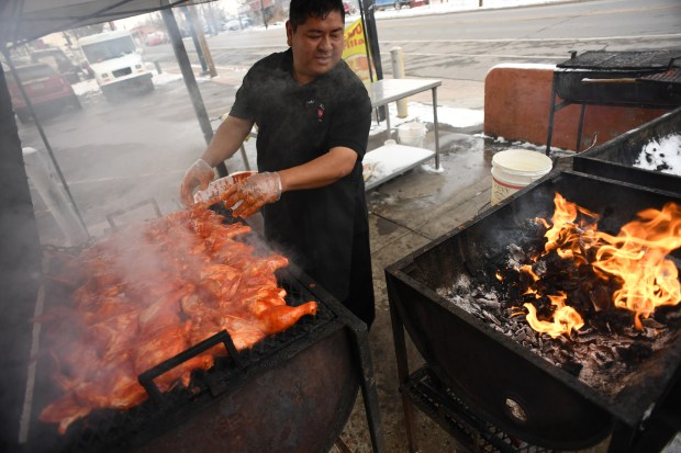 Lalu Aguardo grills chicken outside the ...