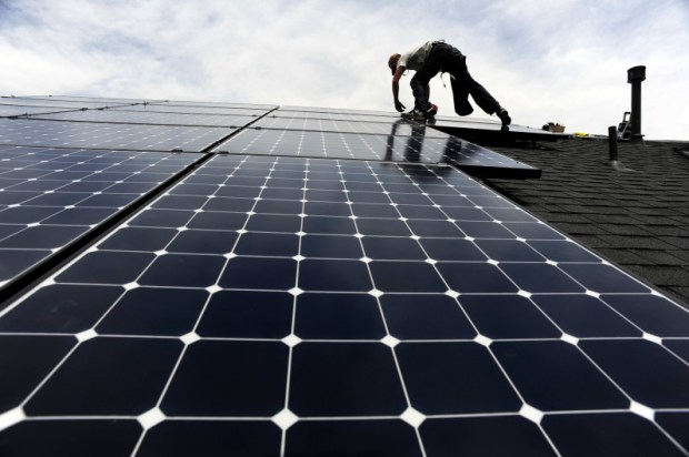 A worker installs solar panels on the roof of a house in Aurora in 2016.