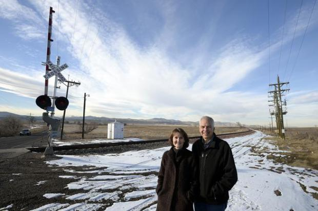 Jim and Kathy Haselmaier pose for a photo Wednesday near the railroad tracks and crossing at 57th Street in north Loveland. The two invented Train Alert, a system to tell commuters when a train is coming and the approximate time it will cross major arterials.