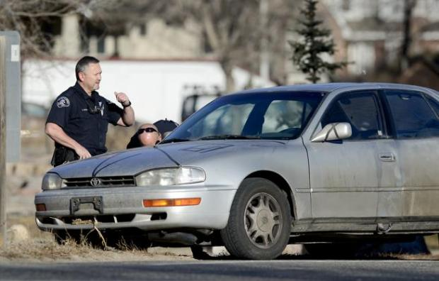 Boulder County sheriff's deputies examine a car driven by a robbery suspect near 61st Street and Valmont Road on Thursday morning.