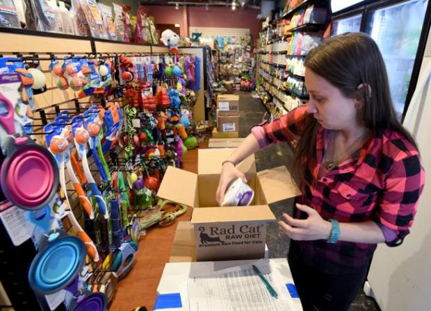 Ashlei Salsbery puts away a new shipment at Whole Pets at the story in the Basemar Shopping Center in Boulder on Wednesday.
