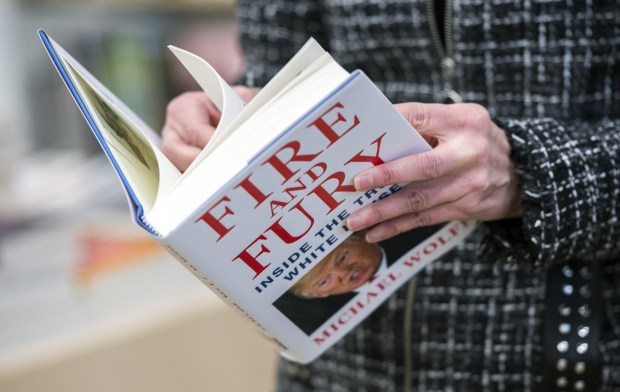 """A man holds a copy of the book """"Fire and Fury: Inside the Trump White House"""" by Michael Wolff after buying it at a bookstore in Washington, D.C., on Jan. 5."""