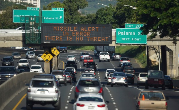 """In this Jan. 13 photo provided by Civil Beat, cars drive past a highway sign that says """"MISSILE ALERT ERROR THERE IS NO THREAT"""" on the H-1 Freeway in Honolulu. State emergency officials announced human error as cause for a statewide announcement of an incoming missile strike alert that was sent to mobile phones."""
